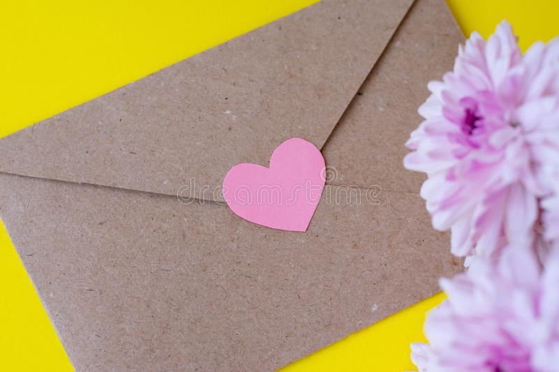 Love envelope with pink chrysanthemum flowers with pink heart on bright yellow background stock photos