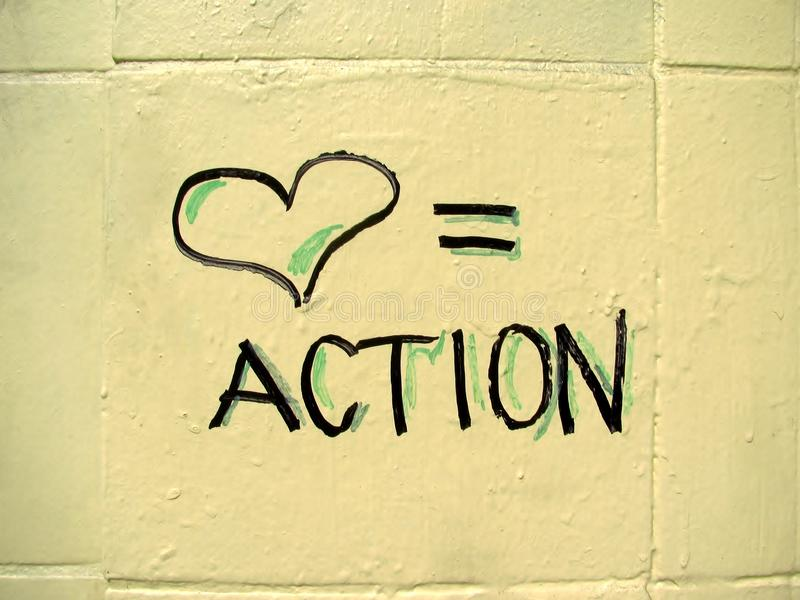 Love equals action sign. Written on the wall royalty free stock photo