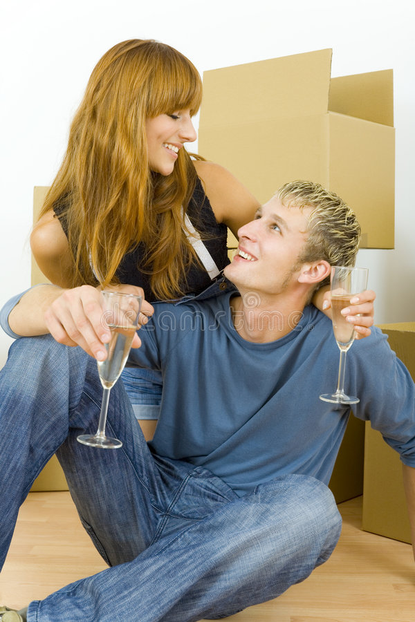 Love in the eyes. Young couple sitting on the floor in flat. They're looking happy. Celebrating removal with champagne. Looking at each other royalty free stock photos