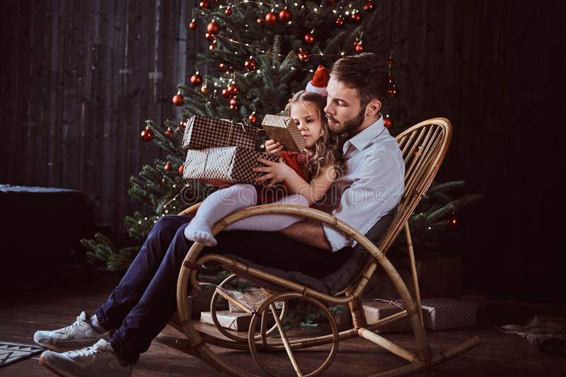 Dad and daughter holding gift boxes while sitting together on a rocking chair near a Christmas tree at home. royalty free stock image
