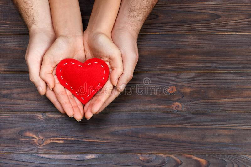 Love, family concept. Close up of man and woman hands holding red rubber heart together stock photography