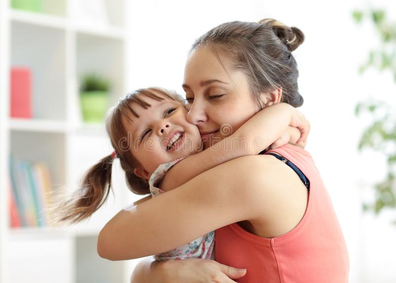 Love and family people concept - happy mother and child daughter hugging at home. Love and family concept - happy mother and child daughter hugging at home royalty free stock images