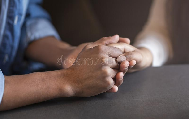 Cropped image of mixed race couple in love holding hands royalty free stock photo