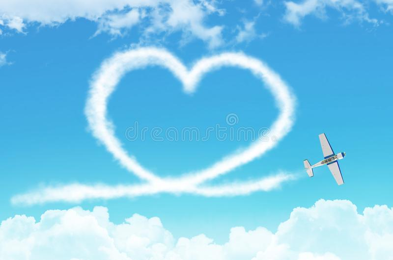 Love figurative heart from a white smoke trail light-engine airplane among the clouds. stock images