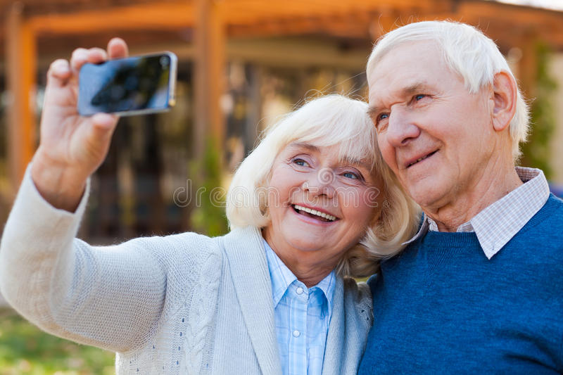 Love in focus. Happy senior couple bonding to each other and making selfie while standing outdoors stock image