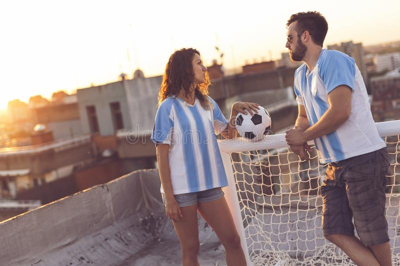 Love and football. Couple in love wearing football jerseys, standing on a building rooftop after a match and enjoying a beautiful sunset over the city stock photo