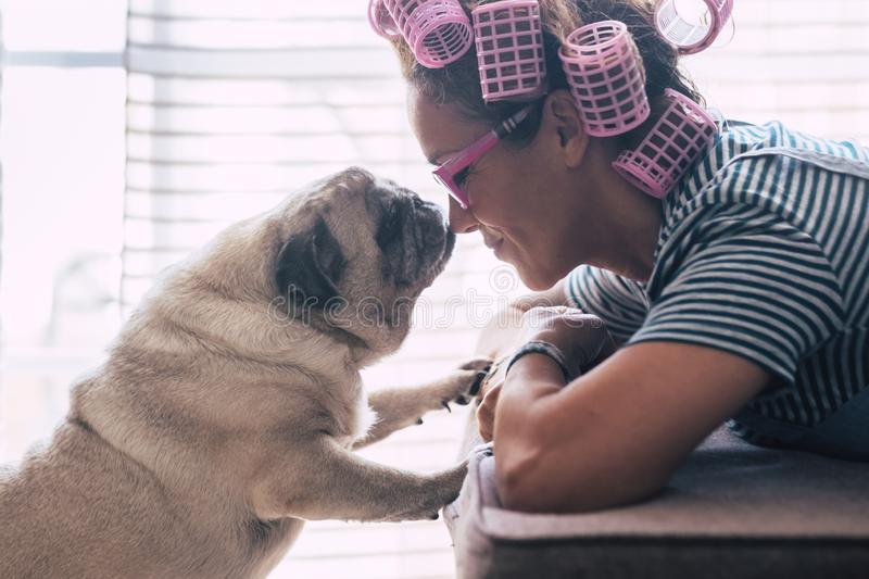 Love and friendship concept with pretty caucasian young woman lay down on the sofa at home and lovely adorable pug dog kissing her stock photography