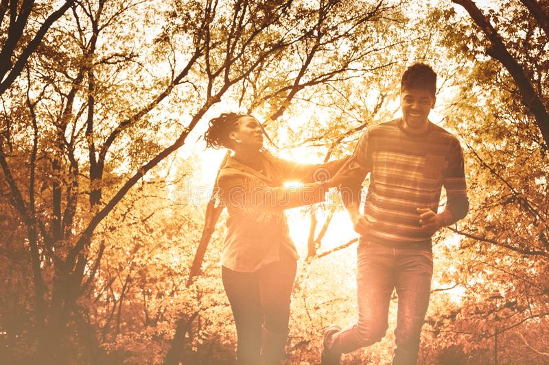 Love is fun. Smiling happy African American couple running and catching in park royalty free stock images