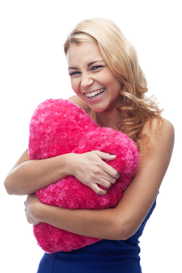 Love is a happiness. Laughing girl with heart shaped pillow on isolated white royalty free stock photo