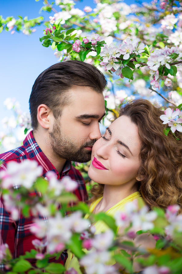 love and happiness - close up portrait of beautiful couple kissing in blooming garden stock photography