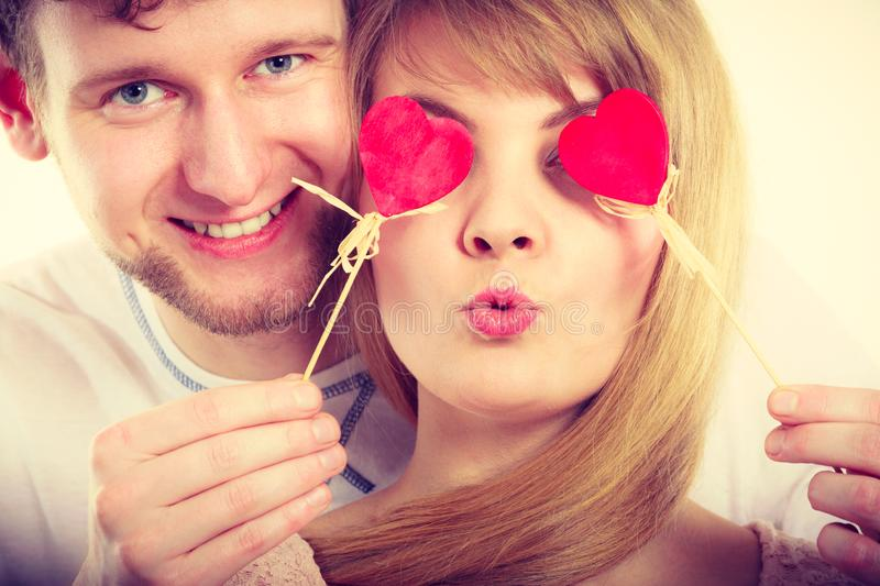 Couple blinded by their love. Love and happiness concept. Cheerful enjoyable young couple with little small hearts on sticks covering women men eyes. Lovers royalty free stock photography