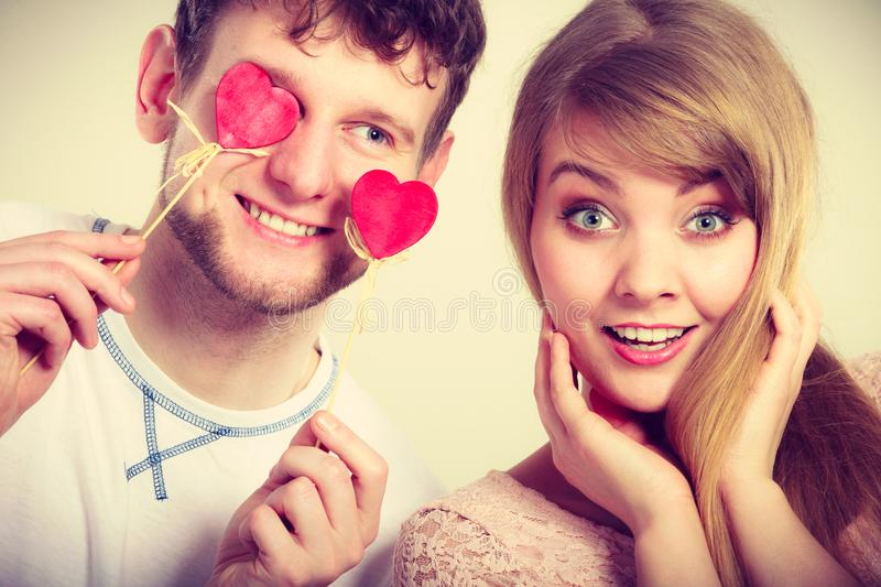 Couple blinded by their love. Love and happiness concept. Cheerful enjoyable young couple with little small hearts on sticks covering women men eyes. Lovers royalty free stock images