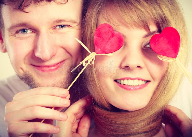 Couple blinded by their love. Love and happiness concept. Cheerful enjoyable young couple with little small hearts on sticks covering women men eyes. Lovers royalty free stock photo