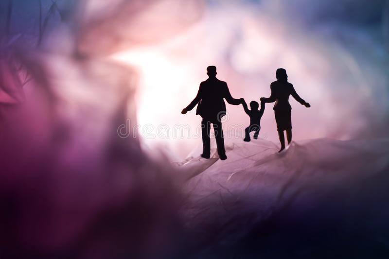 Love and Happy Family. Exploration for Children and Parent. Miniature of Father, Mother and Son holding Hands and Walking on a stock photo