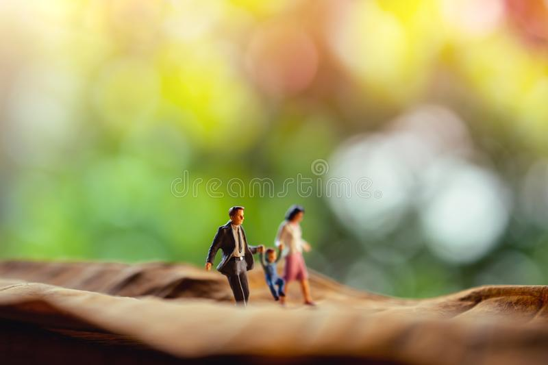 Love and Happy Family. Work Life Balance Concept. Miniature of Father, Mother and Son holding Hands and Walking on Dry Leaf stock photo