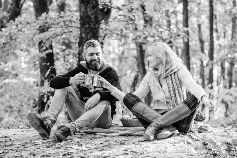 This is love. happy woman and bearded man drink hot wine. couple in love relax in autumn forest with tea or coffee stock photo