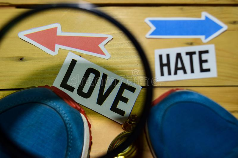 Love or Hate opposite direction signs in magnifying with sneakers and compass on wooden. Vintage background. Business, education and finance concepts stock photos