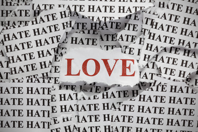 Love and Hate. Torn pieces of paper with the word Hate and word Love in red color. Concept Image. Close-up royalty free stock photography