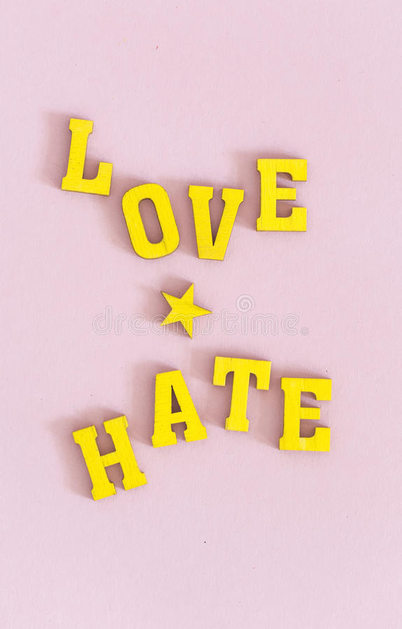 Love and hate. Words love and hate in yellow wooden letters on pink background royalty free stock image