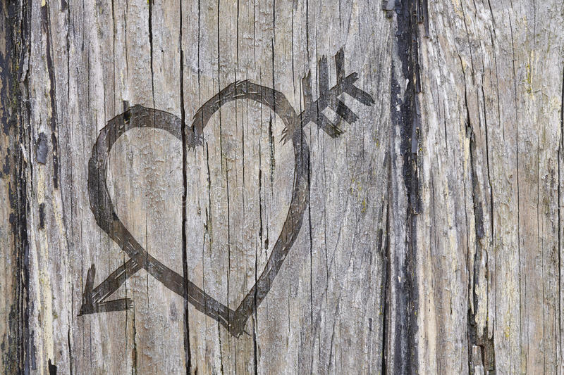 Love heart and arrow graffiti carved into wood. Love heart and arrow graffiti carved into old wood royalty free stock photos