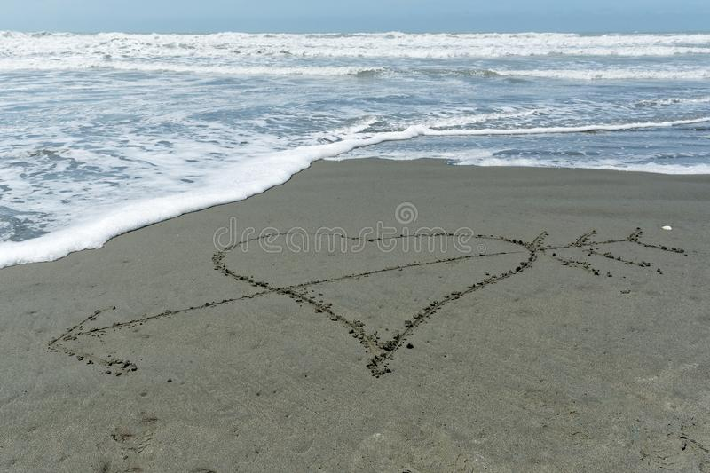 A love heart drawn in the sand is pierced with cupid`s arrow stock image