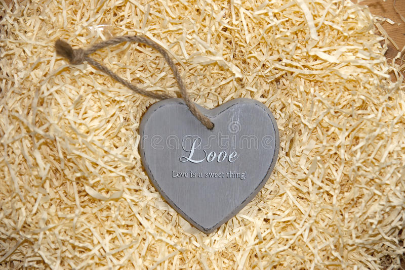 Love heart in grey saying love is a sweet thing. Single grey wooden love heart in a love nest made of straw inscribed love is a sweet thing stock photos