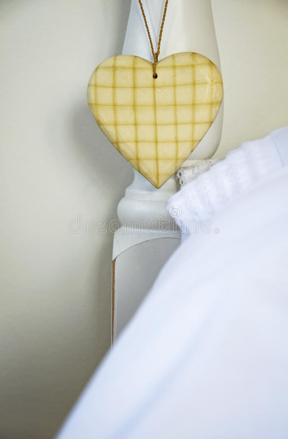 Love heart hanging on bed post royalty free stock photography