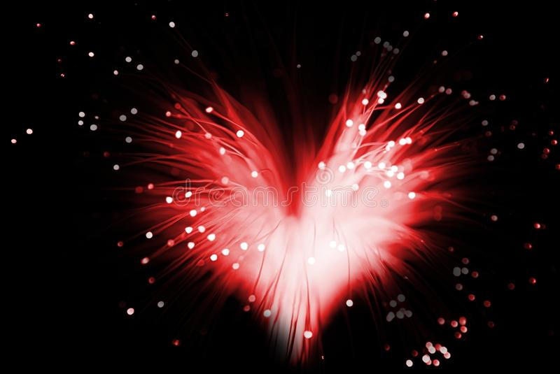 Love heart. Red colored abstract heart made from fibers lights in darkness ( love concept royalty free stock image
