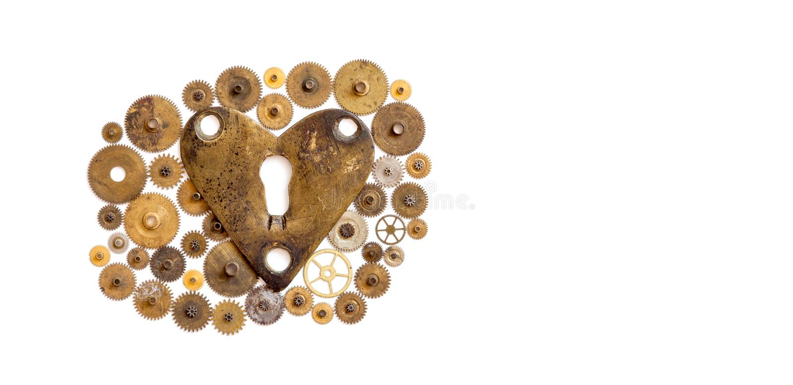 Love heart steampunk machinery ornament on white. Aged bronze keyhole heart shape with many textured cogs gears wheels stock photography