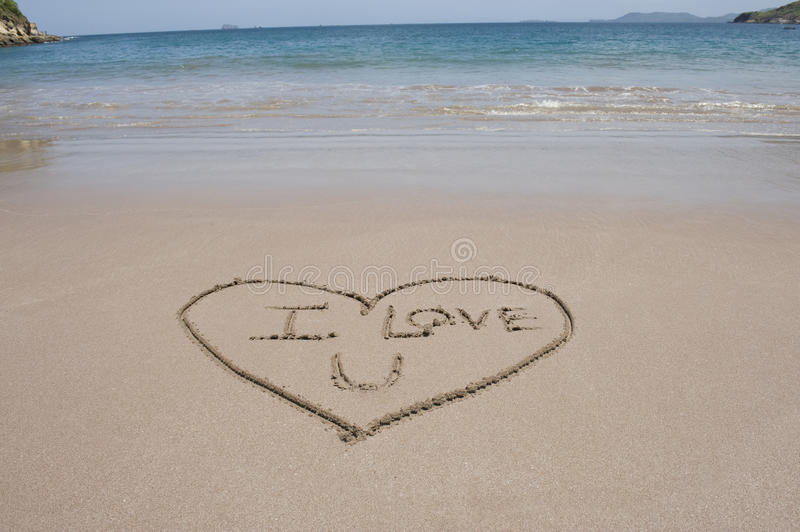 Love heart and words sand beach costa rica. Big love heart in sand with words i love u inside on costa rican beach near blue water royalty free stock images
