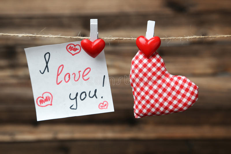 Love hearts hanging on rope on the brown wooden background royalty free stock images