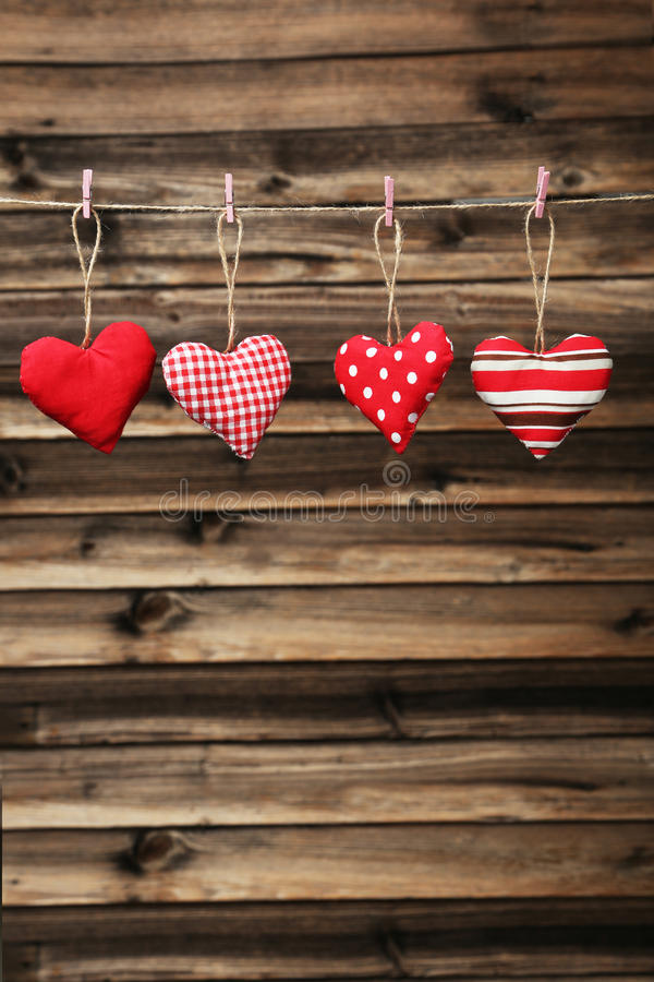 Love hearts hanging on rope on a brown wooden background stock photos