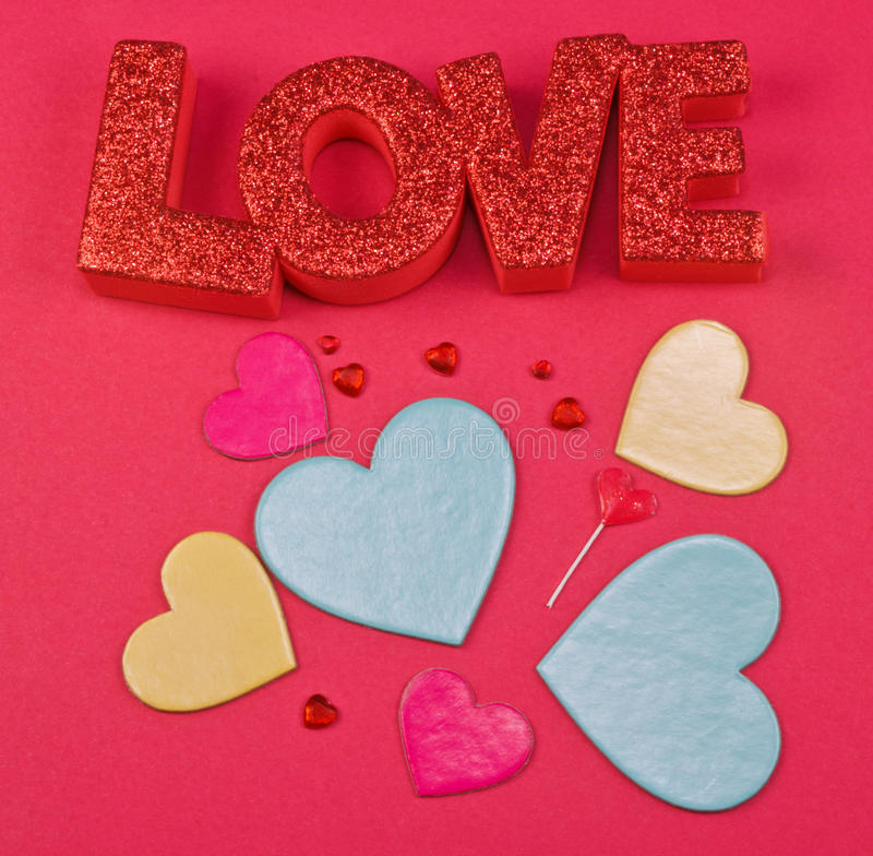 Love and Hearts on red background. The word Love with multicolored hearts on a red background royalty free stock image
