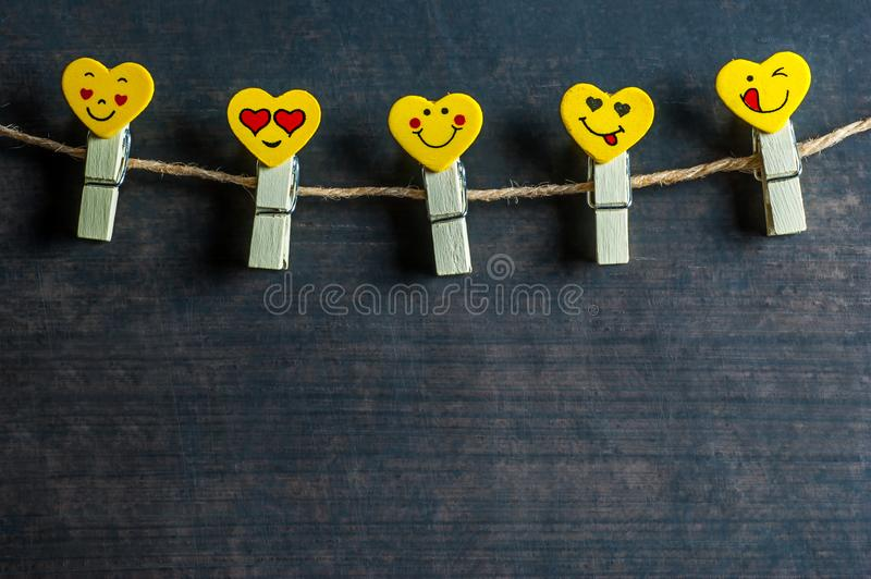 Love Hearts yellow emotions or emoticons clothespins or pegs on a rope on wooden rustic vintage background. Happy valentines day. St. Valentine concept stock photography