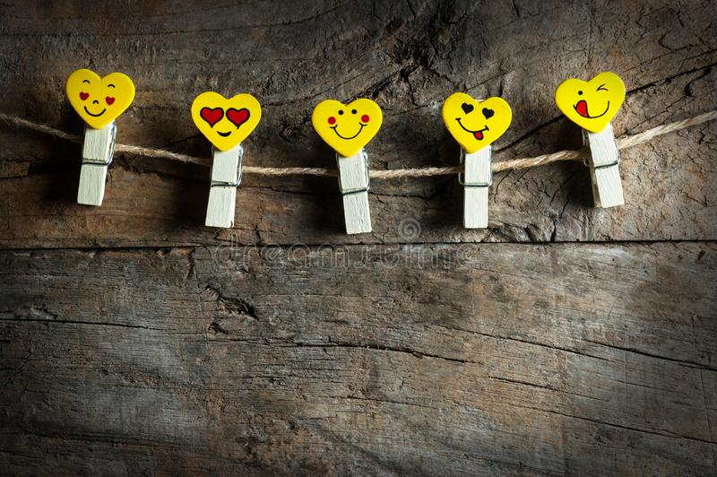 Love Hearts yellow emotions or emoticons clothespins or pegs on a rope on wooden rustic vintage background. Happy valentines day. St. Valentine concept stock photos