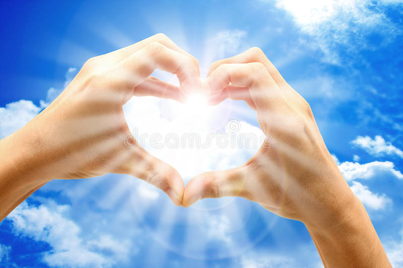 Love from heaven. Sun ray shine through a heart shape formed by two hands