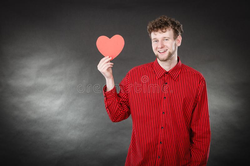 Boy in love with red heart. Love and help from people. Charming lovely man with red paper heart persuade to be good helpful hopeful. Valentines Day or charity stock images