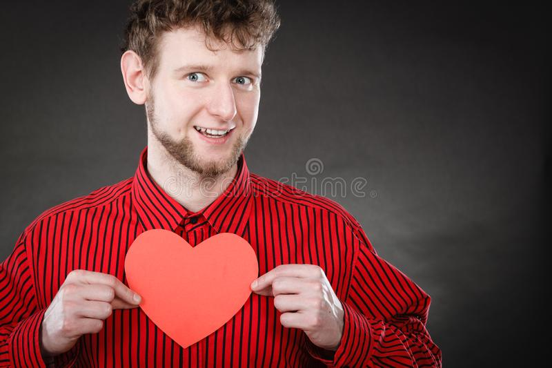 Boy in love with red heart. Love and help from people. Charming lovely man with red paper heart persuade to be good helpful hopeful. Valentines Day or charity stock photo