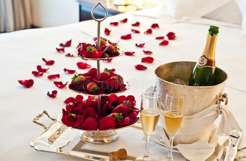 Love: Honeymoon Suite. Honeymoon suite with chocolate strawberries and an opened bottle of champagne royalty free stock photos