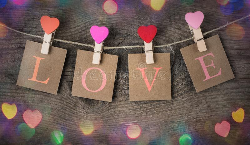The love inscription and red heart clips hanging on natural cord for Valentine Day. royalty free stock images