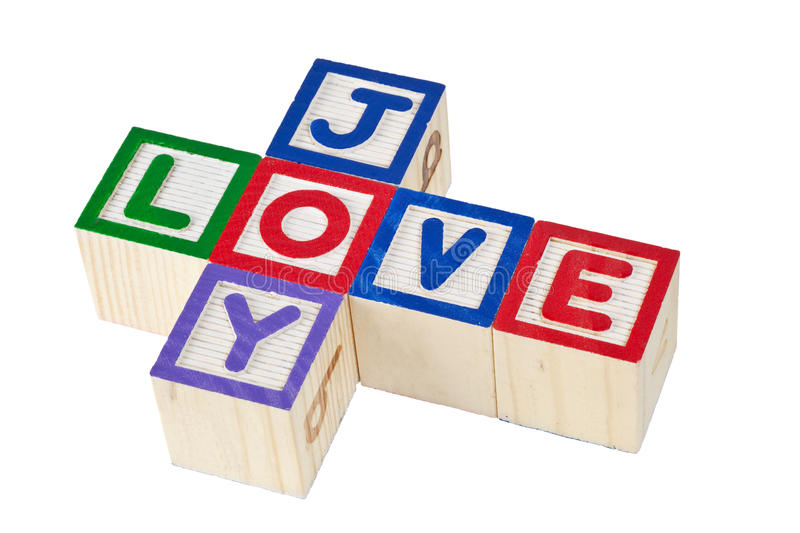 Love and joy. Wooden blocks forming the words love and joy isolated on white background stock photos