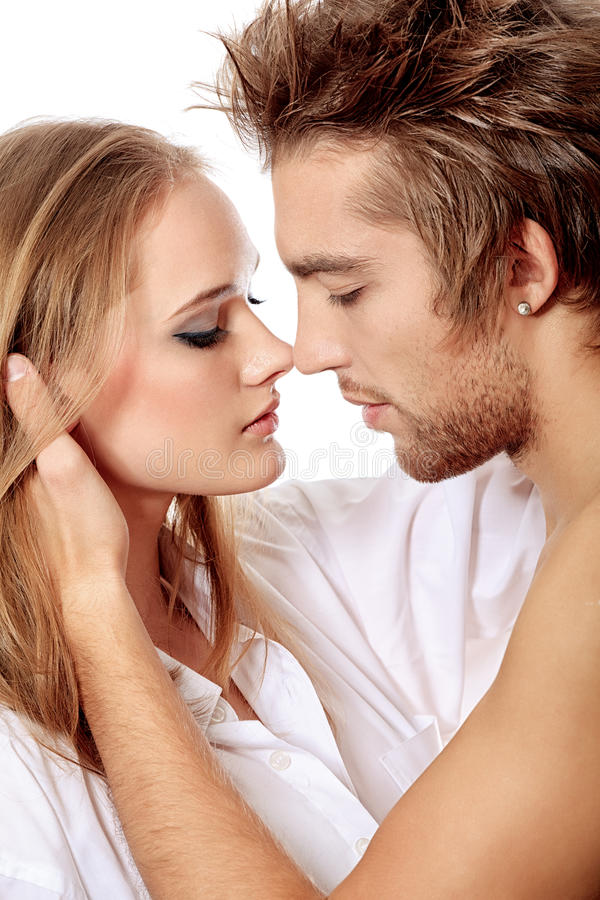 Love kiss. Shot of a passionate young people in love. Isolated over white stock images