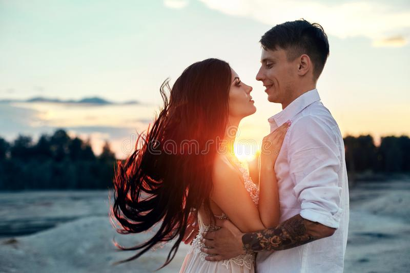 Love kiss and hugs in love couples at sunset in the evening sun, a walk through the mountains and hills. Sensual and gentle loving stock photo