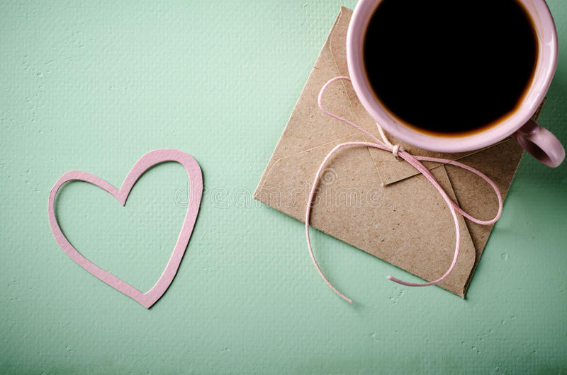 Love letter, envelope and pink cup of coffee. Valentines card. Horizontal, flat lay. Love letter, envelope with paper heart and pink cup of coffee. Valentines royalty free stock photo