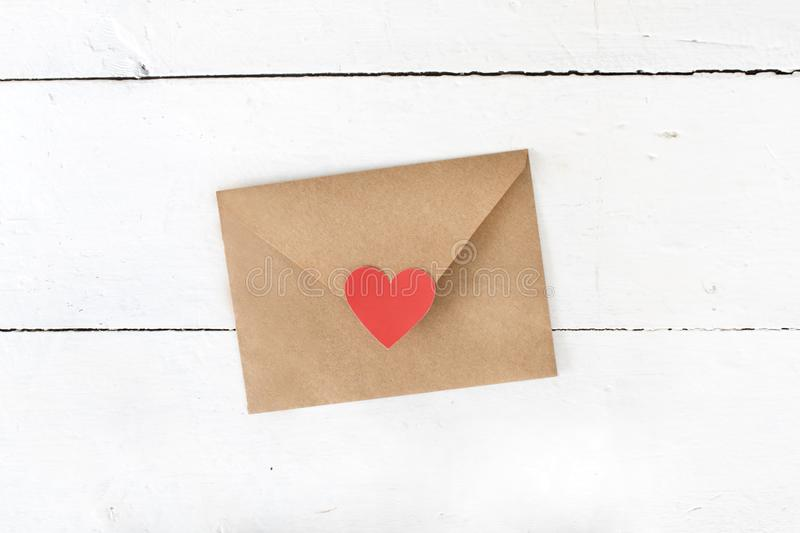 Love letter envelope with red heart on white wooden background. royalty free stock photography