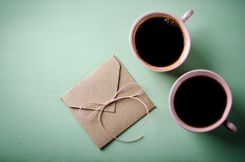 Love letter, envelope and two pink cups of coffee. Valentines card. Horizontal, flat lay. Top view stock photography