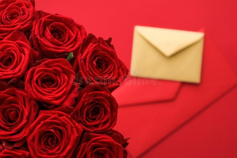 Love letter and flower delivery service on Valentines Day, luxury bouquet of red roses and card envelopes on red background royalty free stock photos