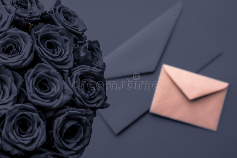 Love letter and flowers delivery on Valentines Day, luxury bouquet of roses and card on charcoal background for romantic holiday stock photos