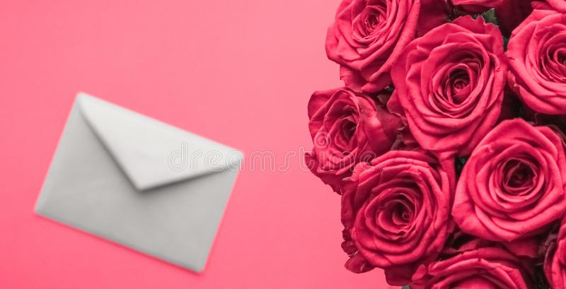 Love letter and flowers delivery on Valentines Day, luxury bouquet of roses and card on pink background for romantic holiday stock photography