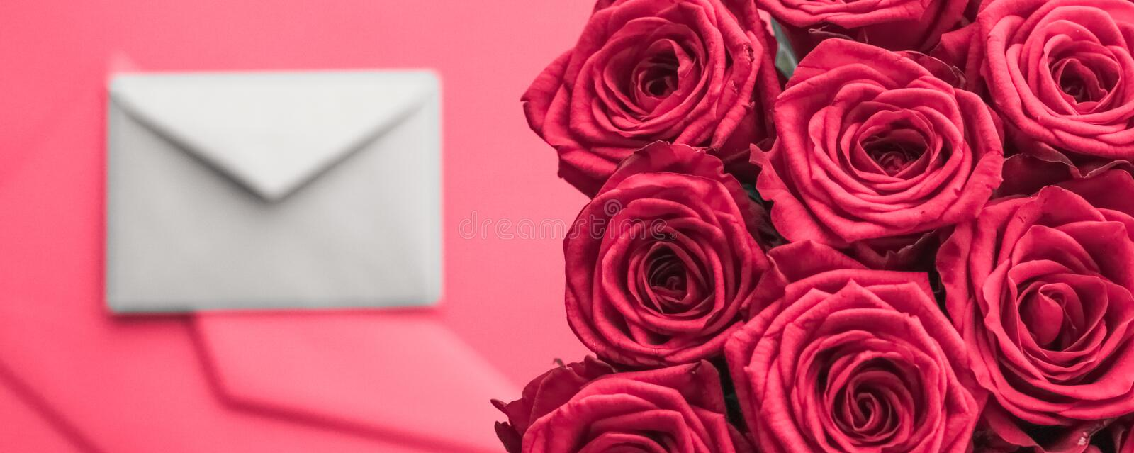 Love letter and flowers delivery on Valentines Day, luxury bouquet of roses and card on pink background for romantic holiday stock photos
